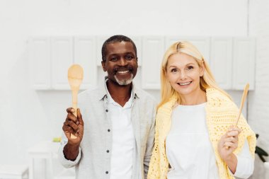 cheerful smiling couple holding wooden spatulas at kitchen