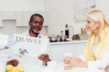 african american man reading newspaper while smiling mature woman drinking tea