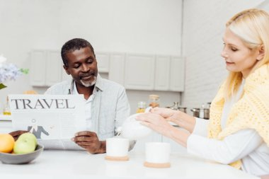 african american man reading travel newspaper while blonde mature woman pouring tea in cups