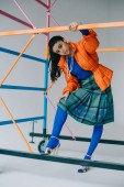 Fotografie stylish girl in orange winter jacket, checkered skirt and blue tights posing near colorful scaffold in studio