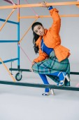 Fotografie fashionable african american female model in orange winter jacket, checkered skirt and blue tights posing near colorful scaffold in studio