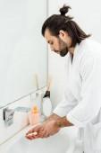 Fotografie adult handsome man in bathrobe washing hands in bathroom