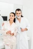 Aranyos pár fehér fürdőköpennyel, mosolyog a fürdőszobában