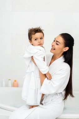 Mother laughing and looking at toddler son in white bathrobe stock vector