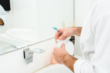 cropped view of male hands holding toothpaste and toothbrush in bathroom