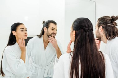 adult lovely couple looking in mirror in bathroom
