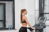 Fotografie Seitenansicht des attraktiven sportlichen Sportlerin training auf Laufband im Fitness-Studio