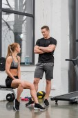 Fotografie athletic sportsman and sportswoman looking at each other in gym