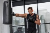 handsome muscular boxer exercising with punching bag in gym