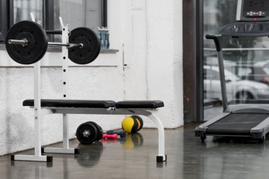 treadmill, barbell and weights in modern gym