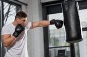 Photo side view of handsome muscular boxer exercising with punching bag in gym