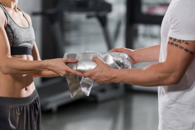 cropped image of trainer giving boxing gloves to boxer in gym
