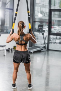back view of muscular sportswoman working out with suspension straps in gym