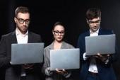 Fotografie Skupina podnikatelů práci s notebooky dohromady izolované na černém