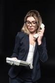 schöne junge Geschäftsfrau hält Telefon isoliert auf schwarz