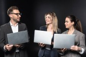 Fotografie group of happy business people working with laptops together isolated on black