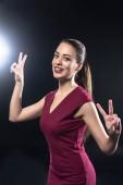 krásná mladá žena v červených šatech ukazuje míru ve znamení na kameru na černém pozadí