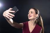 Fotografie lächelnde junge Frau nehmen Selfie mit Smartphone auf schwarz
