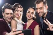Detailní záběr šťastný skupiny přátel, přičemž selfie s smartphone během party na černém
