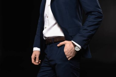 cropped shot of businessman in stylish suit with wrist watch isolated on black