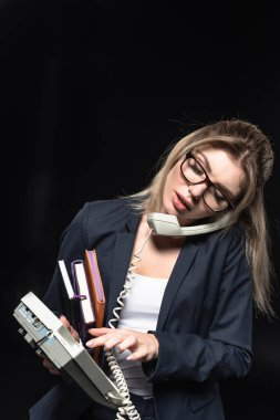 overworked young businesswoman with notebooks talking by phone isolated on black