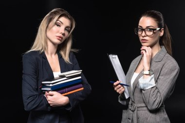 confident young businesswomen isolated on black