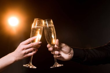 cropped shot of couple clinking glasses of champagne under golden light