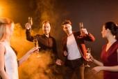 Skupina usmívající se přátel, přípitky šampaňským během party