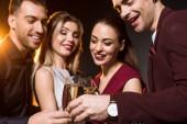Skupina přátel, cinkání, sklenky na sekt při večírku na černém pozadí