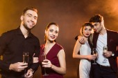 šťastné mladé páry s sklenky na sekt stojící pod zlatým světlem během party