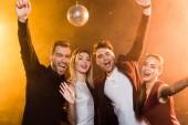Skupina přátel, při pohledu na fotoaparát a slaví během sváteční večírek