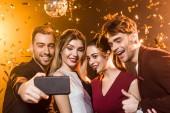 Skupina happy přátel, přičemž selfie s smartphone během party