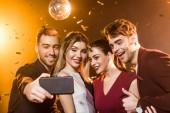 Skupina usmívající se přátel, přičemž selfie s smartphone během party