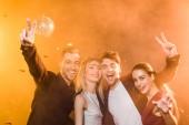 Skupina happy přátel při pohledu kamery a zobrazení mírové gesto během party