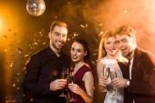 šťastné skupina přátel držení sklenice šampaňského a při pohledu na fotoaparát během party