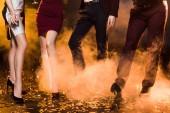 oříznuté shot skupiny přátel, stojící na černé podlaze pokryté zlaté konfety během vánoční večírek