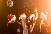 Skupina přátel v santa klobouky tančí během vánoční večírek