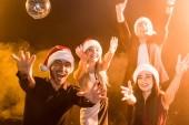 Skupina přátel v santa klobouky slaví Nový rok pod žlutým světlem