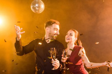 happy flirting couple with champagne having fun during party under golden light while confetti falling around