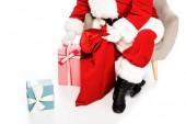 Fotografie oříznuté shot santa Claus sedí v křesle s dárky izolované na bílém
