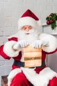 Santa claus sedí na prsou a drží pergamen s wishlist