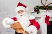 Santa claus drží pergamen a čtení seznamu přání