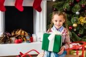 nettes Lächeln auf den Lippen Kind auf Schlitten sitzen und halten Weihnachtsgeschenk