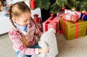entzückende glückliches Kind spielen mit Teddybär an Heiligabend