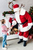 Fotografie high angle view of little child giving rolled wishlist to santa