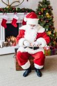 pohled z vysokého úhlu santa Claus drží válcované pergamen s seznamu přání