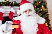 Fotografie Santa claus drží kreditní kartu a při pohledu na fotoaparát