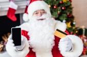 Weihnachtsmann hält Kreditkarte in der Hand und zeigt Smartphone mit leerem Bildschirm
