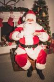 Santa Claus drží desku s cookies a sklenice mléka