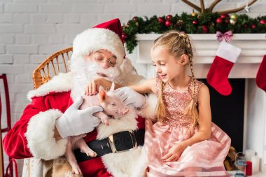 santa claus and cute little child playing with adorable pig at christmas time